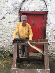 'Hackling' This is the final step in dressing the flax. The fibres are split and straightened by being drawn through a graded series of combs or 'hackles' The long fibres are used for weaving and the shorter coarser fibres which catch on the comb (called 'tow') can be used to make rougher cloth. The woody waste matter, known locally as 'shous' was often used as firewood. Courtesy Fred Faulkener